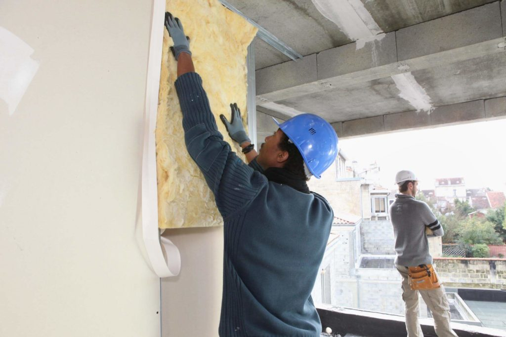 Worker installing insulation in a newly built home