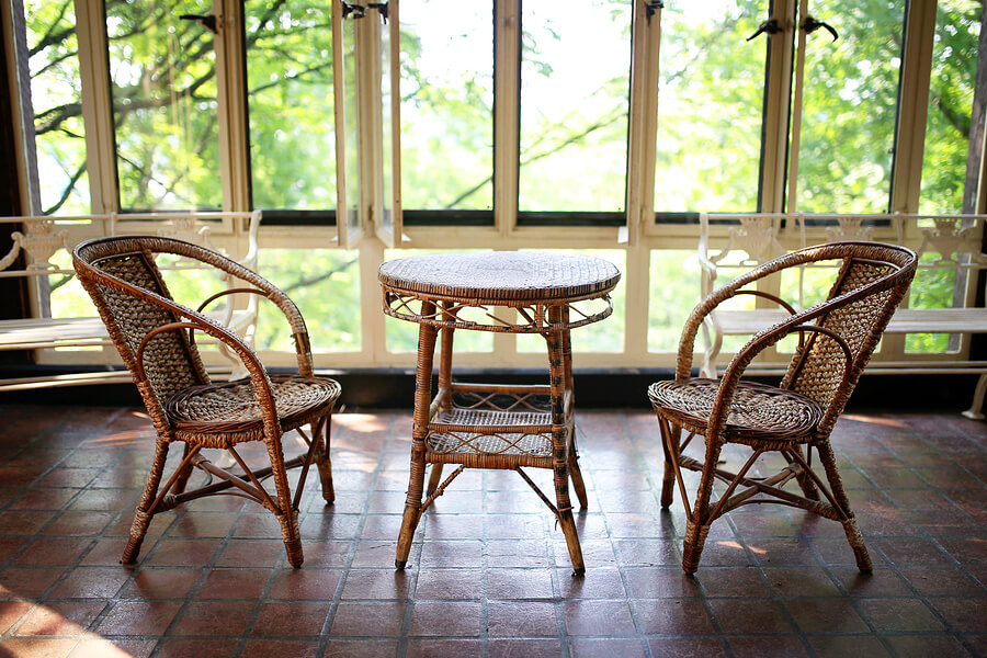 Old wicker bistro table and chair set siting in a sunroom addition of a large historic house