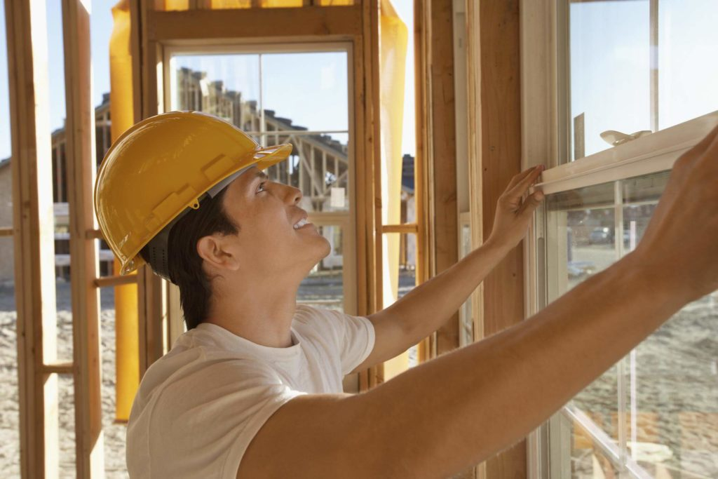Worker installing a window in a modular home addition