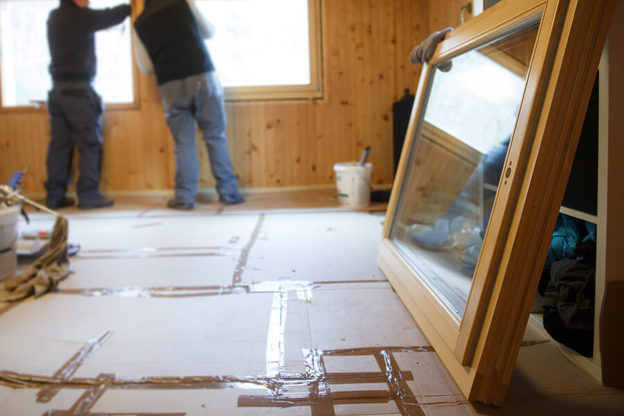Workers installing new three pane wooden windows in a modular home addition